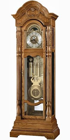 """Howard Miller Nicolette 611-048 Oak Grandfather Clock  This stately floor clock offers a graceful bonnet pediment with book-matched olive ash burl and a decorative shell and vine overlay. An astrological blue moon phase draws attention to the polished brass dial, which features cast corner and center ornaments, a silver chapter ring with applied brass Arabic numerals and an Ambassador Collection inscription.   Size: H. 90-1/4"""" W. 30-1/2"""" D. 17-3/4"""""""