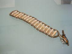 Bracciale a coni di colore rosa con conteria di colore bronzo. Chiusura con moschettone argentato.