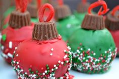 Use your favorite cake ball recipe.  Coat with red and green candy chocolate shell. Sprinkle. Add a small Reese's cup and a piece of string licorice for the top