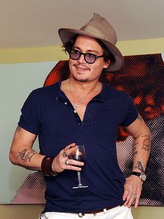 """He's like a fine wine! Johnny Depp – who has a tattoo reading """"wino forever"""" – samples some red Tuesday, while perusing the works of artists Jordi Molla and Domingo Zapata at an exhibition held at West Hollywood's Chateau Marmont. From:Star Tracks: Wednesday, October 12, 2011"""
