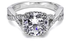 From our Dantela Collection, this unique setting creates a look that is a beautiful juxtaposition of modern, yet traditional; classic, yet unconventional. Diamonds enhance both the look and shape of this platinum Engagement Ring. Pave dazzles along criss-crossing shoulders, and a diamond crown gives the round center stone a cushion-cut look. 2627RD