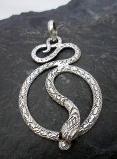$55.00~Large Sterling Silver Textured Snake Pendant  ~Designed in Nepal. There is so much detail in the texture on both the front and back of this Sterling Silver Snake Pendant.  This large Snake is curved and coiled around as if slithering downward.  The tail curves slightly around the large bale and the head of the Snake lifts up slightly over it's body. Tiny Garnet beads are used  for the eyes. Please click on the picture for more details.