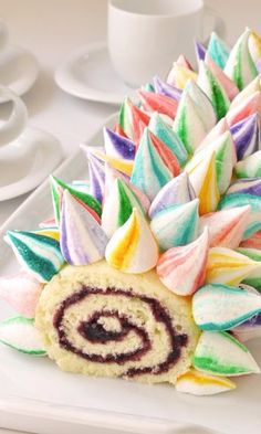 Unicorn Cake Roll-Brightly colored meringue unicorn horns cover this sweet vanilla and blackberry jam cake roll. The results are simply magical! This sweet treat would make a great dessert for a kid's birthday party or spring or summer slumber party with friends. It would also be fun for Easter brunch with it's pastel colored meringue horns.