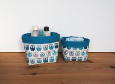 Ces deux paniers sont en coton enduit imprimé de chouettes bleues et grises dun côté. De lautre, ils sont en coton uni bleu pétrole.  Lavantage du coton enduit est quil est imperméable et se nettoie dun coup déponge. Ils sont triplés avec un entoilage pour plus de tenues. Ils peuvent vous servir comme rangement dans votre salle de bain, comme vide-poche, ou rangements divers et variés tout en décorant votre intérieur. Ils feront aussi leur petit effet dans une chambre denfant, autour de la…