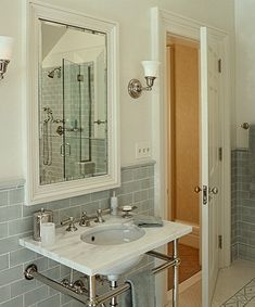 Beautiful ivory & gray blue bathroom design with ivory walls paint color, gray blue glass subway tiles backsplash, 2 leg marble washstand and ivory mirror.