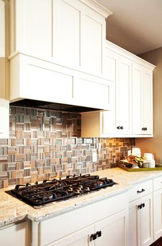 a full wall subway patterned silver travertine backsplash is surrounded by custom built. Black Bedroom Furniture Sets. Home Design Ideas