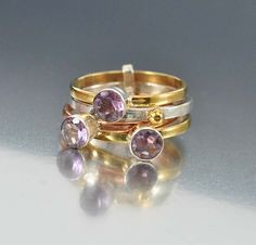 Modernist stacking rings set with large open back genuine purple amethyst gemstones. The tricolor metal rings in gold, copper and sterling silver, have three half carat amethyst gemstones with the ste