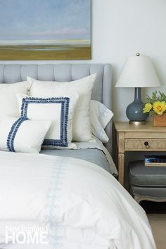 serene bedroom, abstract art, upholstered headboard, blue and white