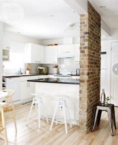 la cocina es de color blanca,hay un plan de trabajo blanco y sillas blancas y  muebles de cocina blanco