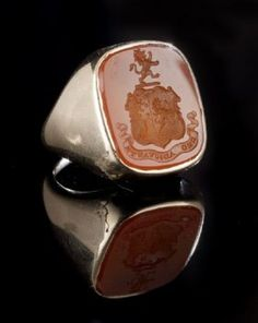 """Fourteen Karat Yellow Gold Carnelian Intaglio Armorial Ring, first half 20th century, with a rounded rectangular carnelian ingaglio engraved with an armorial with a crest of a lion rampant and the motto """"Deo Adjuvante"""" (for Milles?) bezel set in a conforming frame with integral shoulders narrowing to a plain shank, size 6.5, 13.2 gr. (including carnelian) sold for $750"""