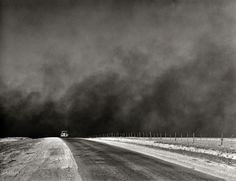 """March 1936. """"Heavy black clouds of dust rising over the Texas Panhandle"""" — evidence of the forces that were driving thousands of farm families in Texas and Oklahoma to the West Coast in the great Dust Bowl migration chronicled in """"The Grapes of Wrath."""" Medium format negative by Arthur Rothstein. View full size."""