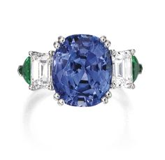 PLATINUM, SAPPHIRE, EMERALD AND DIAMOND RING Centered by a cushion-cut sapphire weighing 8.09 carats, flanked by two emerald-cut diamonds weighing approximately 1.20 carats and two triangular-shaped emeralds weighing approximately 1.00 carat