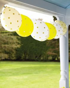 Balloon dotted with office stickers, strung across porch with twine...