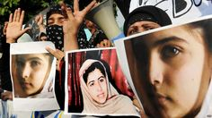 Pakistani civil society activists carry placards and papers with a photograph of the gunshot victim Malala Yousafzai in Islamabad on October 10