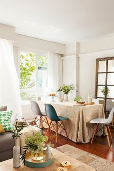 Comedor abierto al salón en blanco con sillas de colores y gran espejo de pie