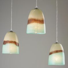 """Strata Art Glass Pendant Light arth, sea and clouds seem to unite in this brown, aqua, and cream art glass pendant light. Its breathtaking beauty is not fully realized until lit! Since this glass is hand blown glass, every pendant will be unique and have variations in size, depth of color and width of cream, brown and aqua color bands. 60 watts medium base socket. (approximate dimensions: 9""""-11.5""""Hx6""""-7""""W)"""
