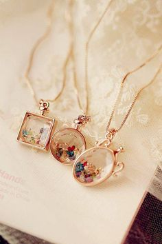Gold lockets with small gemstones inside.