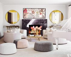 Mirrors by Wüd Furniture Design frame a Jean-Michel Basquiat screen print in the living room. On Yves Klein cocktail table, Tom Dixon gold vase; India Mahdavi sofas in Schumacher bouclé; custom suede poufs.