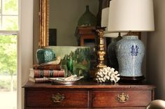 Dressertop vignette - blue and white lamp, coral, old books, silver dish