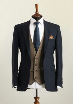 Wedding Suit Hire A mannequin wearing a navy lounge suit jacket with brown check waistcoat and patterned blue tie.A mannequin wearing a navy lounge suit jacket with brown check waistcoat and patterned blue tie. Wedding Suit Hire, Wedding Men, Tweed Wedding Suits, Mens Wedding Style, Blue Wedding Suit Groom, Vintage Wedding Suits, Wedding Ideas, Mens Fashion Suits, Mens Suits