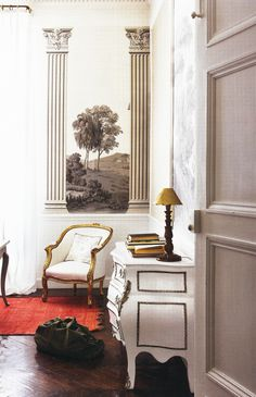 love the dark antiqued gold and white french chair with the gray toile pillow. not a huge fan of the mural or lamp