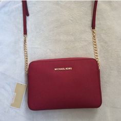 """NWT Michael Kors large jet set travel cross body Brand new. In cherry gold. I'm open to reasonable offers. Saffiano leather. Adjustable cross body strap with 25"""" drop. 9""""W X 6""""H X 2""""D Michael Kors Bags Crossbody Bags"""