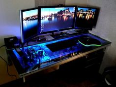 This desk mod, by modder L3p, hides unused computer components away leaving only the essentials: mouse, keyboard, displays, power switch. The glass top lifts up to give easy access to the computer components for upgrading and maintenance. Another neat feature is the fluorescent liquid effect given to much of the hardware, making a neat lighting display in the dark.