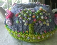SOLD - 800ml garden tea cozie with acrylic flowers, knitted butterfly, tree with multi coloured buds, glass beads as flower centre