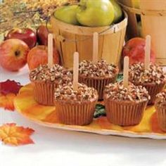 Caramel Apple Cupcakes | Spice cake topped with caramel, sprinkled with peanuts and a popsicle stick in the center to look just like a caramel apple.