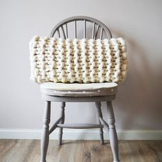 This chunky knit rectangular cushion adds interest and style to a bed or seat and the classic natural white wool suits almost any colour pallet. Each one is made from my studio in devon, handcrafted from start to finish on chunky needles using beautiful merino wool. The tactile stitch adds interest and texture thats irresistibly touchable and the calm and sophisticate natural white colour helps it fit in seamlessly with modern or rustic decor.  A thoughtful present for a stylish friend or a…