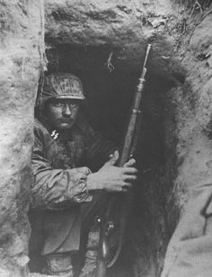 Ostfront aWaffen SS soldier hunker down. Their eyes expression bears more desperation than confidence.