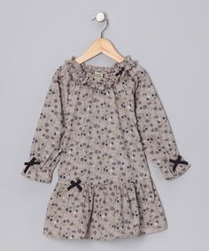 Perfectly prim, this well-made cotton dress features a drop waist and contrasting navy bows. With an elastic neckline, the easy-on piece balances functionality with fancy fashion.