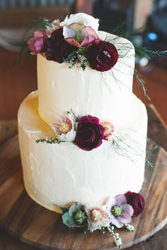White buttercream cake with burgundy flowers for a rustic country wedding | Little Black Bow Photography | See more: http://theweddingplaybook.com/rustic-burgundy-country-wedding/