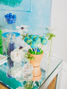 Throw a colorful and eco-friendly party for Earth Day with these globe cake pops, clear glass vases, fresh flowers and blue rock candy