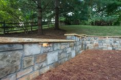 The rear hardscape consists of CMU walls with a Stoneyhurst veneer stone topped with Teakwood caps; natural cleft gold quartzite stone wet laid on concrete; a Raffinato smooth border in beige cream color installed along walkway. The playground area was laid out with safe mulch and owner supplied playground set. The project was completed with lighting and plantings.