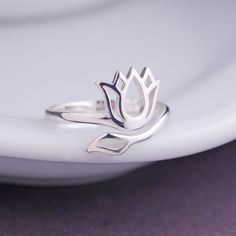 This lotus flower ring is sterling silver and fits most! Adjusts from approximately a size 6 to a size 9. Ready to ship and perfectly pairs with all of our personalized jewelry. Handmade in Thailand.