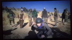 Iraqi soldiers laughing and taking pictures of American reporter overreacting to battle.