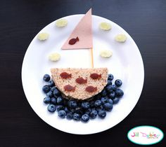 from meet the dubiens      Bologna sandwich cut into a semi-circle for the bottom of the boat. Cut another piece of bologna into a triangle to use as the sail. A thin slice of cheese to attach the sail to the boat. Blueberries for the water, cucumber clouds, and fruit leather fish details. I cut the fish and clouds out of adorable bento cutters I got from All Things for Sale (link in my sidebar).    Have a great weekend everyone!