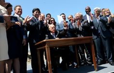 Gov. Jerry Brown, center, and others including Former Gov. Arnold Schwarzenegger, far left, celebrate after Brown signed the climate bill AB 398 on Treasure Island in San Francisco, Calif., on Tuesday, July 25, 2017. The bill strengthens the state's cap-and-trade program, which would have expired without legislative action. (Jane Tyska/Bay Area News Group)