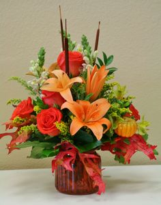 Vase of fall flowers including orange lilies, orange roses and yellow snapdragons. These flowers are made at your local riverside flower shop - Willow Branch Florist of Riverside