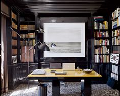 Lacquered walls bring polish to the library of cosmetics executive Aerin Lauder Zinterhofer's Long Island home. The dark palette is enlivened with a Chip Hooper photograph, a floor lamp by Serge Mouille, and a graphic patterned carpet by AM Collections.   - ELLEDecor.com