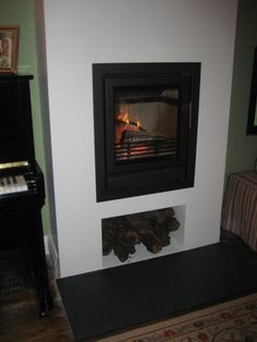 The finished hole in wall solid fuel fireplace with log store