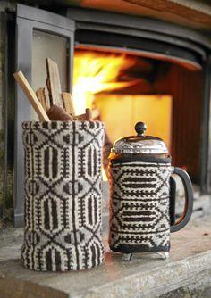 Gamle gensere og andre strikkeplagg som ikke lenger brukes, har fått nytt liv som varmere til både te- og kaffekanner. Her holder presskannen seg glohet med påkledning laget av et fint strikket erme. Kantene har fått påsydd svart bånd, mens det er festet borrelås under hanken.
