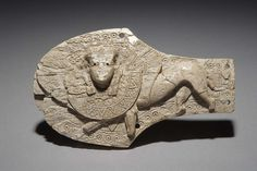 Ivory horse blinker ornament from Nimrud with carved decoration showing a winged human headed lion wearing an elaborate collar. 8th – 7th century BC. Phoenician style © The Trustees of the British Museum