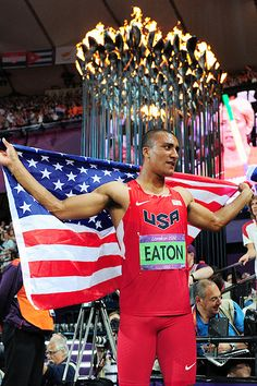 Ashton Eaton draped himself with the American flag in front of the Olympic flame after winning gold in the decathlon.
