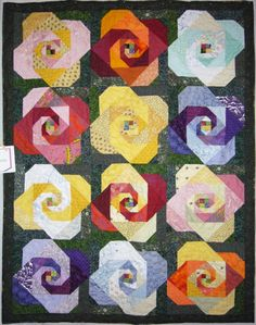 Rose Garden, by Peter Stringham Pattern Name: Modified Snail trail. Wall Quilt 60 x 50 Machine Pieced, Machine Quilted by Laurena McDermott