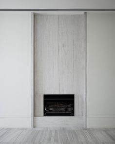 Discrete stone fireplace at Cassell Street Residence by B.E Architecture referencing the buildings travertine facade throughout the interiors
