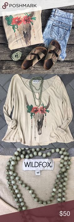 WILDFOX Bullhead Henley Wildfox Couture Desert Dahlia Lagoon Henley Long-Sleeve Thermal   SOLD OUT STYLE! This oversized top is super cute for all boho babes! This luxuriously soft long sleeve thermal is oversized and features henley style buttons, an A line shape and a rounded hem. A beautiful bovine skull decorated with rosaries and flowers is printed on the front. I just found it in my closet - has a minor stain (see pic 4) Otherwise in good condition! This will also fit large/xl since…