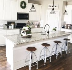 Gray and white kitchen with metal pendant lamps over large marble her planked wood island and caged metal pendants create a beautiful balance of industrial farmhouse style anyone else calling dibs for aloadofball Choice Image