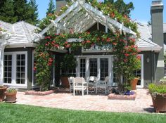 Beautiful white pergola with flowers and brick patio